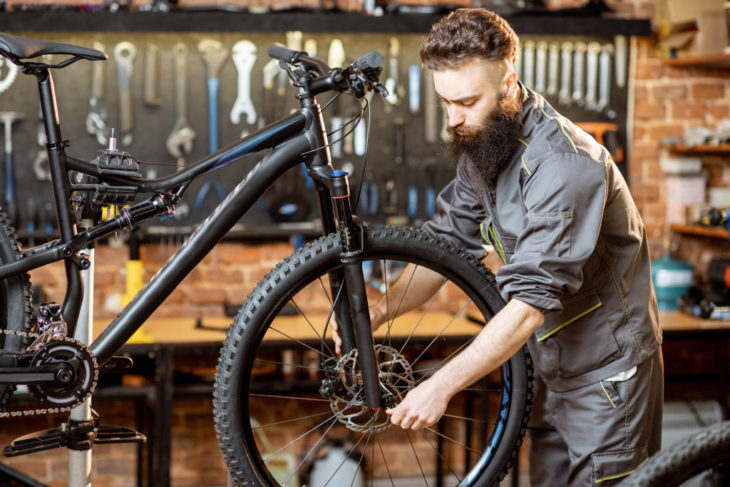 Repairman with bicycle at the workshop